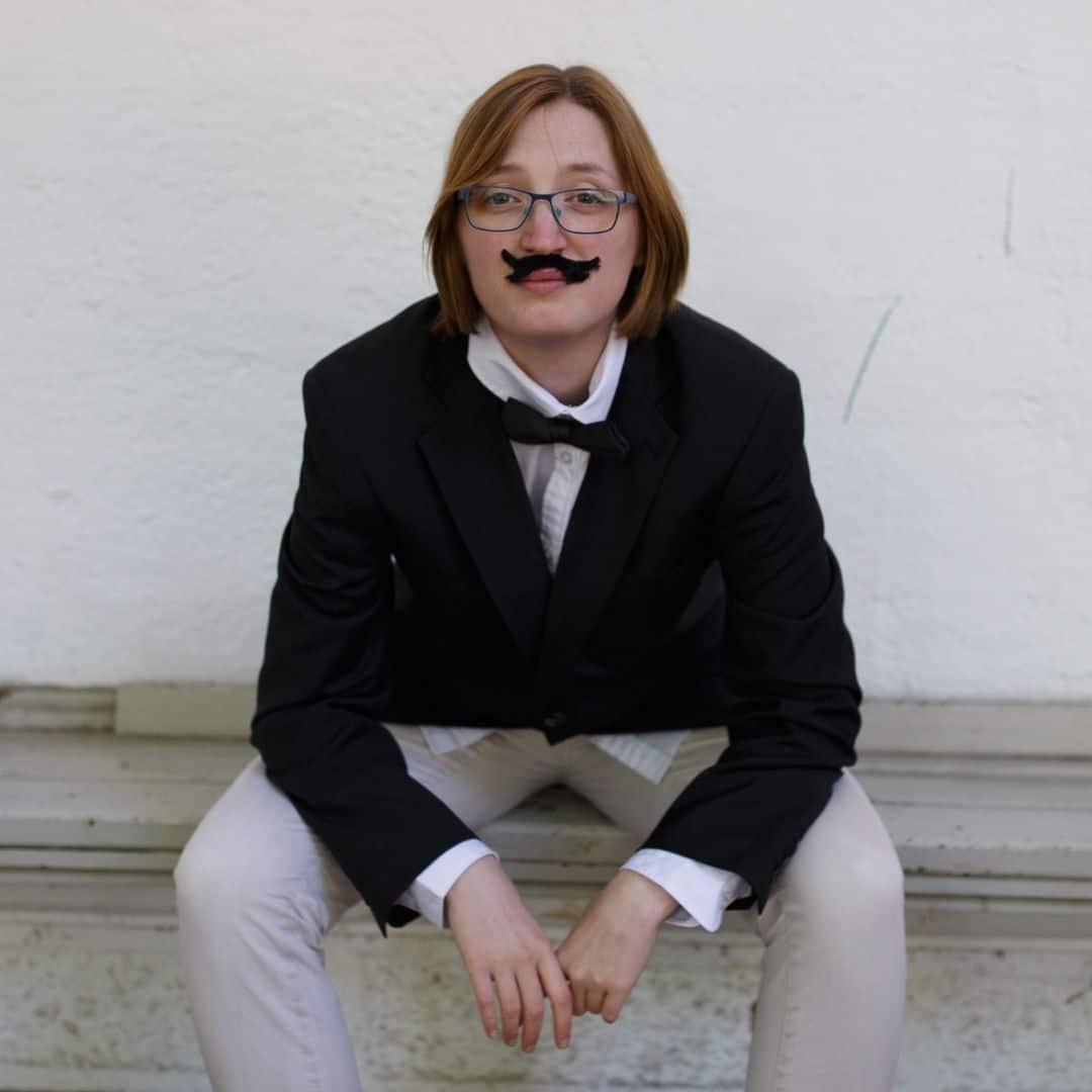 Jane Schmidt als Mann in Anzug und mit Bart
