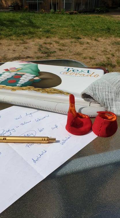 Laptop, Papier und Stift im Freien.